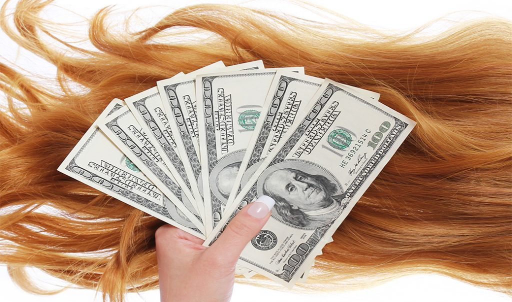 girl's hand holding money against hair extensions