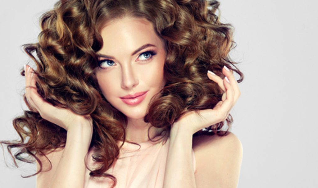 woman with brunette curly hair holding her hair