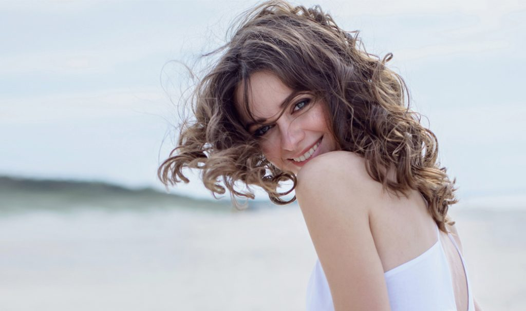 woman with beach waves hairstyle smiling