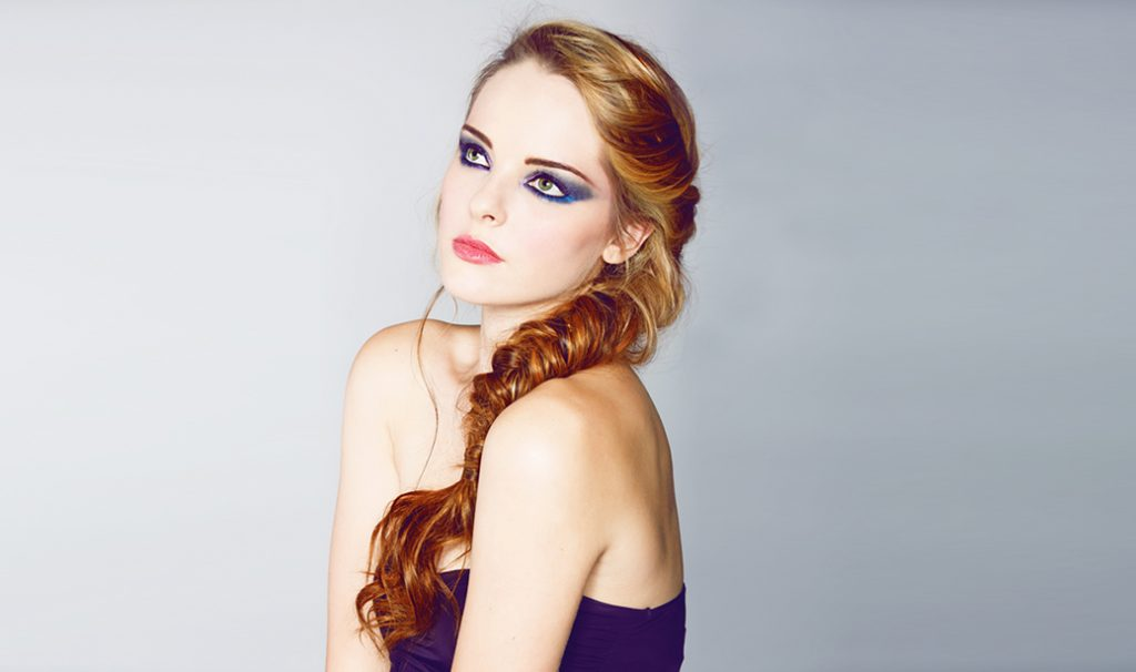 woman with fishtail braid and blue eyeshadow looking upwards