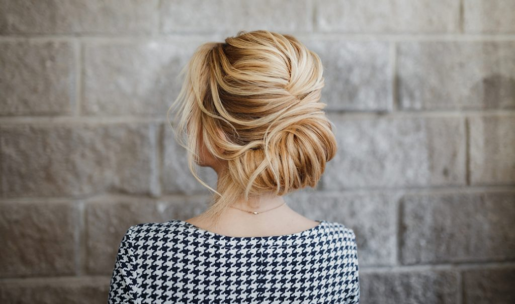 woman with blonde french twist hairstyle in houndstooth pattern shirt showing her back against brick wall background