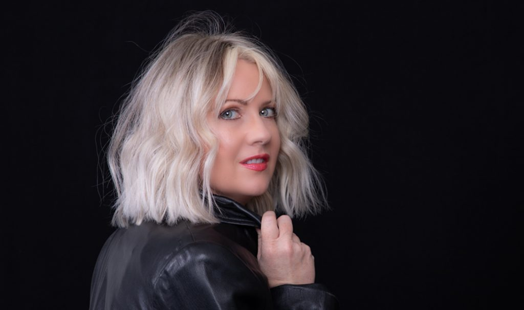 woman with medium length blonde messy hair wearing black leather jacket against black background