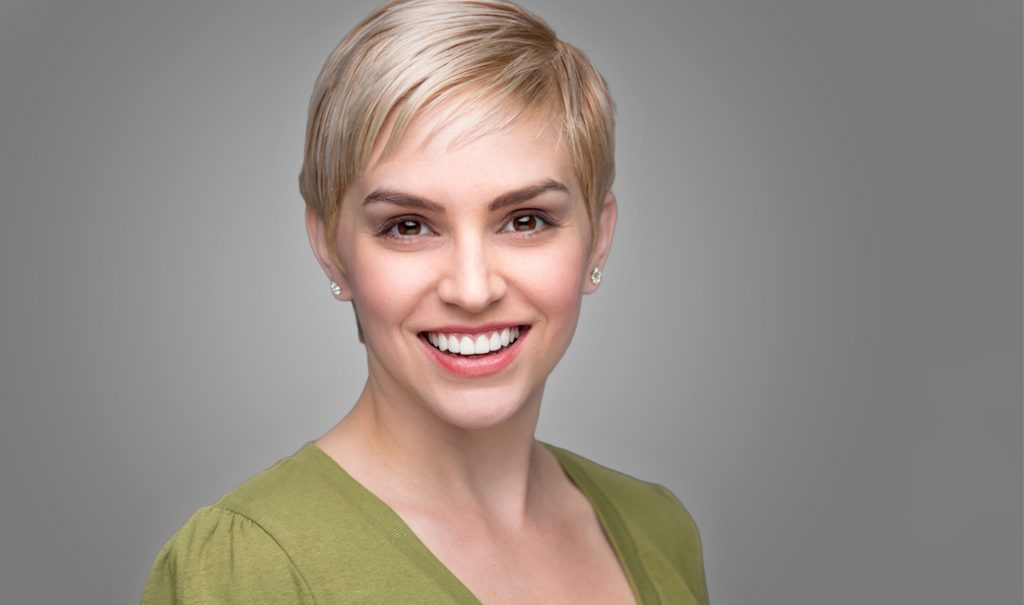 woman with short pixie cut and a big smile against grey background