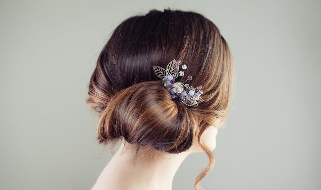woman with side bun hairstyle and floral hair piece
