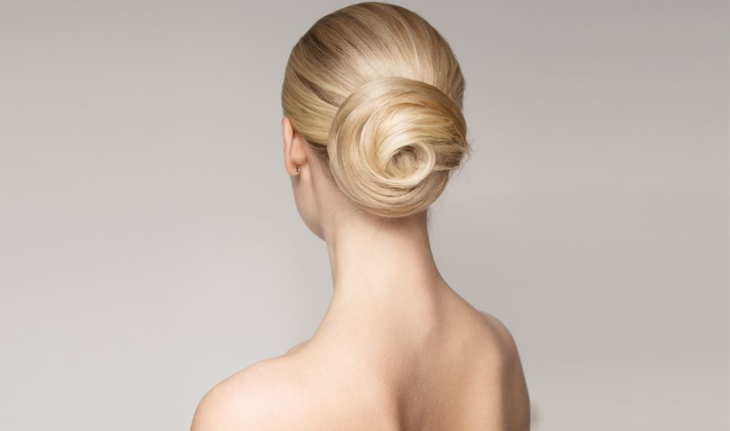 woman with blonde twisted hair bun showing her back