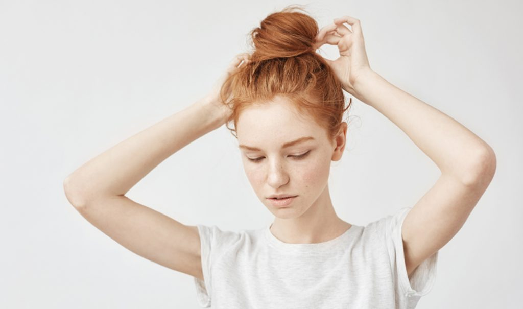 woman in white t-shirt tying her hair up in a bun