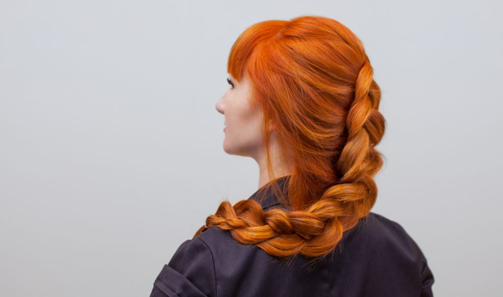 red hair woman with long french braids showing her back