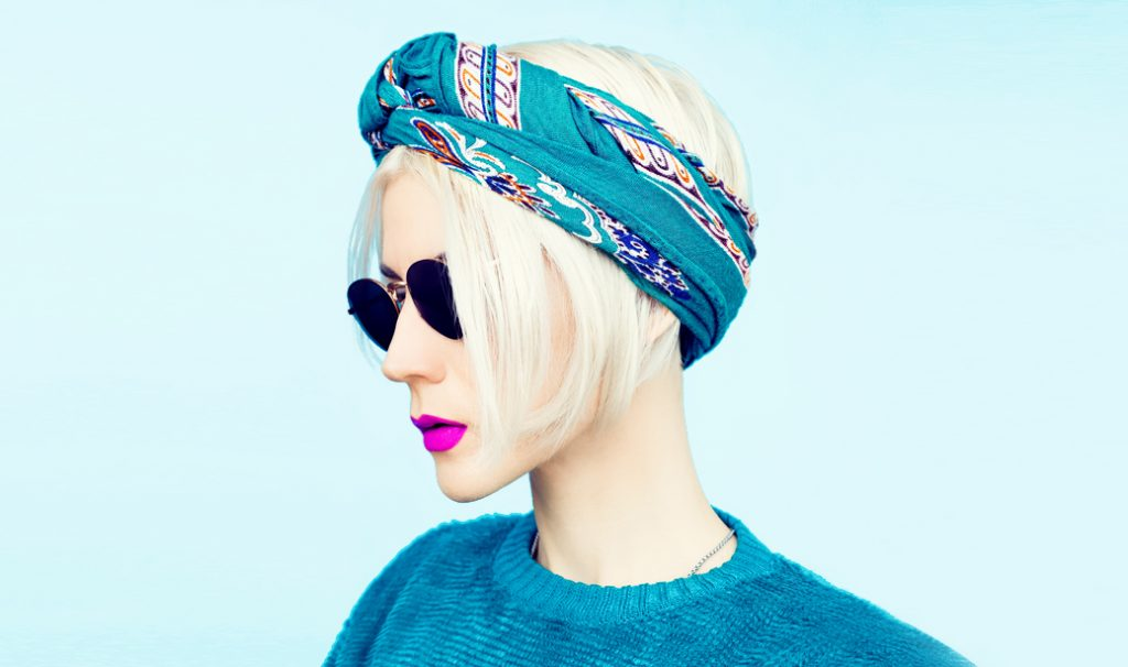 woman with blonde bob hairstyle wearing sunglasses, blue scarf and blue sweater against blue background