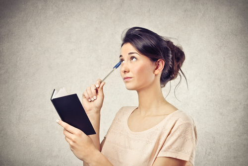 thinking woman holding book and pen and looking upward