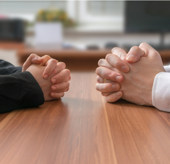two people with clasped hands sat across the table from each other
