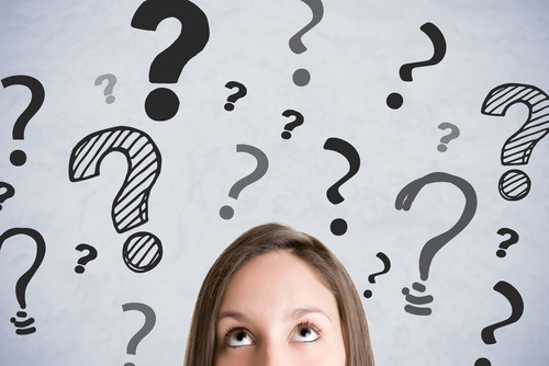 woman thinking and looking upward with many question marks over her head